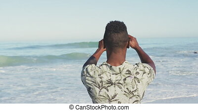 African American taking photo of the sea - Rear view of an ...