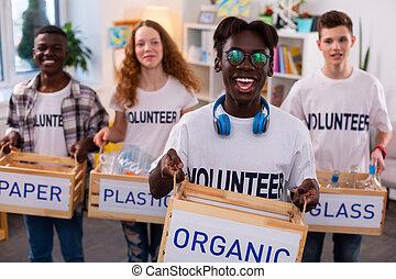 African-American teenager feeling satisfied after sorting waste