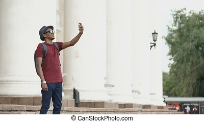 African american tourist man having online video chat using his smartphone camera standing near historical building in Europe