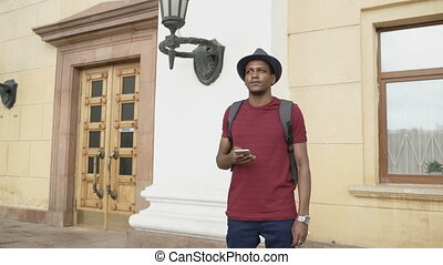 African american tourist man using smartphone online map to...