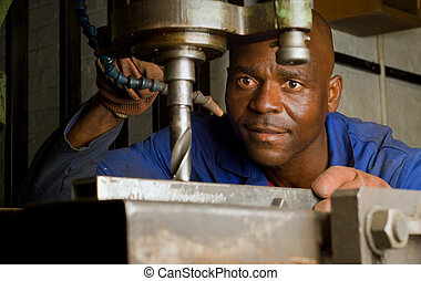 African American with drill press - South African or...