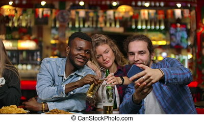African american with european friends sitting in a bar takes a selfie. A large group of friends sits in a barz at one table chatting, drinking beer and taking pictures