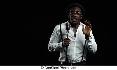 African American with glasses singing and dancing to the music from the microphone. Black background. Slow motion. Close up