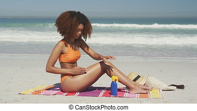 African American woman applying sunscreen at beach