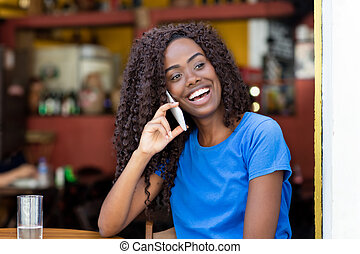 African american woman at bar laughing at mobile phone
