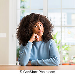 African american woman at home with hand on chin thinking about question, pensive expression. Smiling with thoughtful face. Doubt concept.