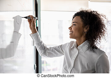 African American woman busy developing business strategy on board