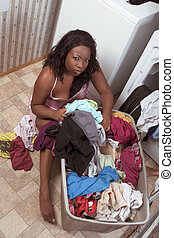 African American woman by basket of dirty laundry - Seminude...