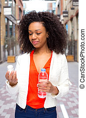 african american woman checking her pills and holding a bottle of water.