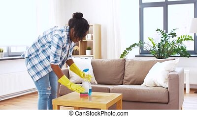 african american woman cleaning table at home - household...