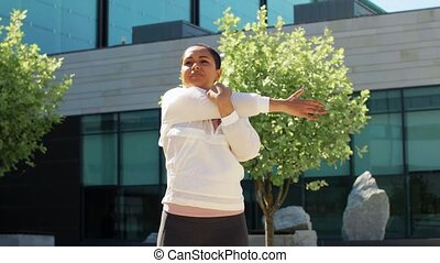 fitness, sport and healthy lifestyle concept - happy smiling young african american woman stretching arm outdoors