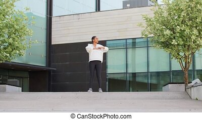 fitness, sport and healthy lifestyle concept - happy smiling young african american woman stretching outdoors