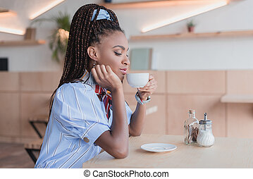 african american woman drinking coffee in cafe