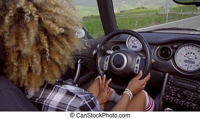 African American Woman Driving A Cabriolet. - View over...