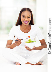 african american woman eating green salad in bed