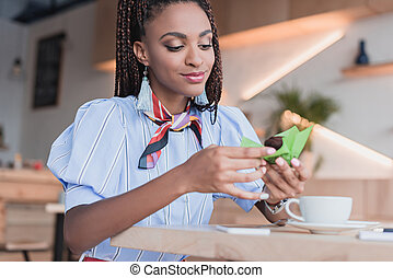 african american woman eating muffin in cafe