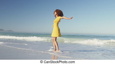 Front view of an African American woman enjoying time in the sun on a tropical beach, turning with her hands raised and smiling, in slow motion
