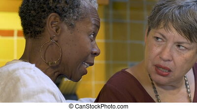 African American woman gossiping with a woman in her 60s -...