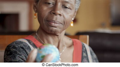 African American woman holding a small world globe and looking at it
