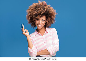African american woman holding credit card in hand.