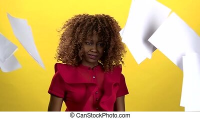 African american holds sheets of paper in her hands and throws them away, she is angry and loses. Yellow background. Slow motion