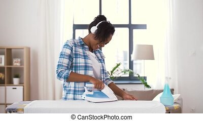 african american woman ironing bed linen at home - people,...