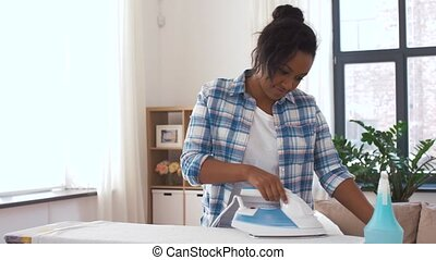 african american woman ironing bed linen at home