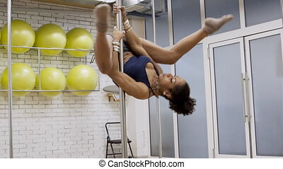 African American woman is riding the vertical pole with her...