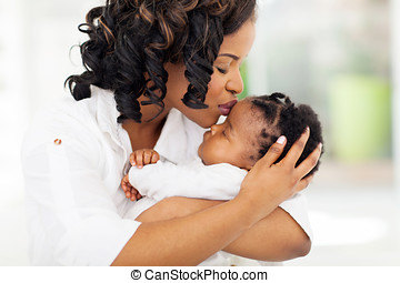 african american woman kissing her baby - loving african...