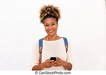 African american woman listening music against white background