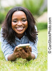 african american woman lying on grass using smart phone