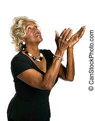 Beautiful african-american woman raising her hands in praise.