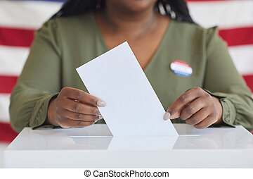 African-American Woman Putting Vote in Ballot Box Close up