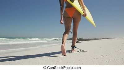 African American woman ready to go surf - Low angle view of ...