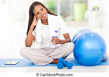 african american woman resting at gym