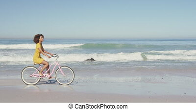 African American woman riding a bike seaside - Side view of ...