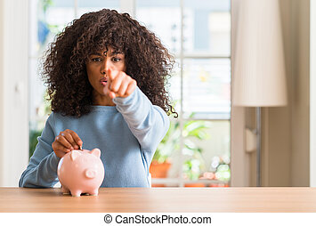 African american woman saves money in piggy bank pointing with finger to the camera and to you, hand sign, positive and confident gesture from the front