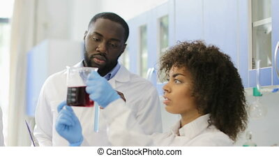 African American Woman Scientific Assistant Hold Chemicals While Scientists Expertise Result Of Experiment In Modern Laboratory