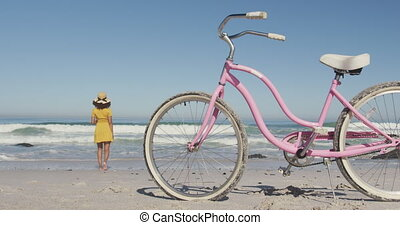African American woman seaside with a bike - Rear view of an...