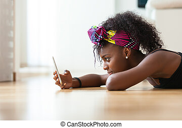 African American woman sending a text message on a mobile...
