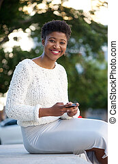 African american woman sending message with cellphone