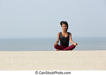 African american woman sitting at beach in yoga pose