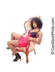 African American woman sitting in armchair.