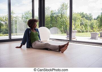 african american woman sitting near window
