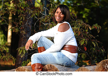 African-American woman sitting on log