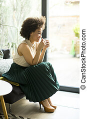 African american woman sitting on sofa with cup of coffee