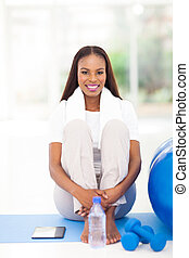 african american woman sitting on exercise mat