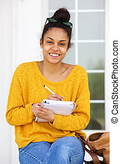African american woman sitting outside writing in book
