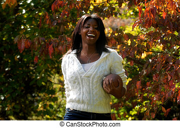 African-American woman smiles with a football