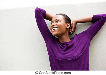 African american woman smiling with hands behind hand